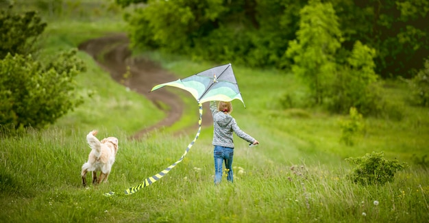 Little girl with dog flying kite