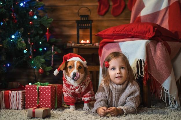 Маленькая девочка с собакой джек рассел терьер дома с елкой, подарками и свечами празднует рождество