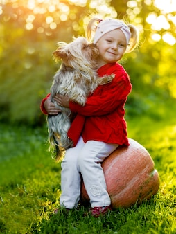 A little girl with a dog sitting on a pumpkin in the autumn park