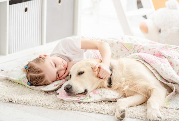 Маленькая девочка с собакой под одеялом