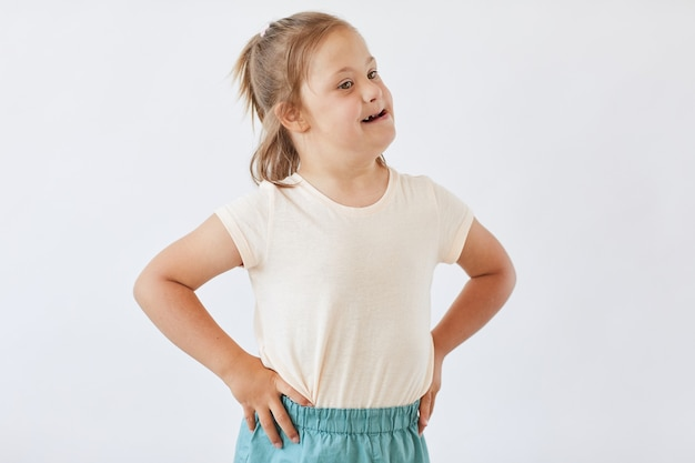 Little girl with down syndrome in casual clothing standing against the white background