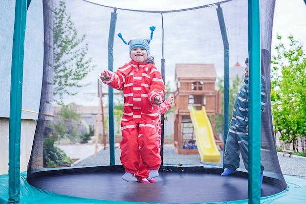 다운 증후군을 앓고있는 어린 소녀가 트램폴린에서 점프합니다. 그녀는 행복합니다. 선택적 초점