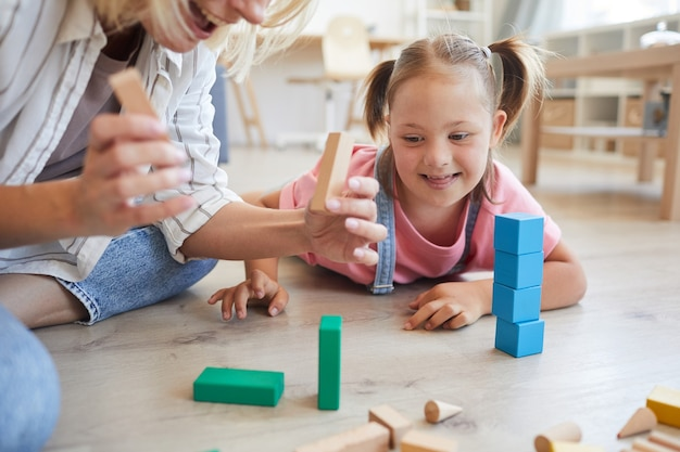 Little girl with down syndrome lying on the floor and watching how her mother building a tower from colored blocks at home