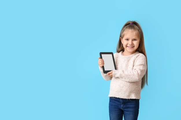 Little girl with e-reader on blue