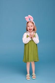 귀와 파란색 표면에 닭고기 달걀 어린 소녀. 부활절