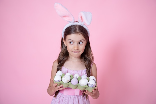 Маленькая девочка с ушами пасхального кролика и подносом яиц в ее руках на розовом фоне студии. концепция праздника пасхи.