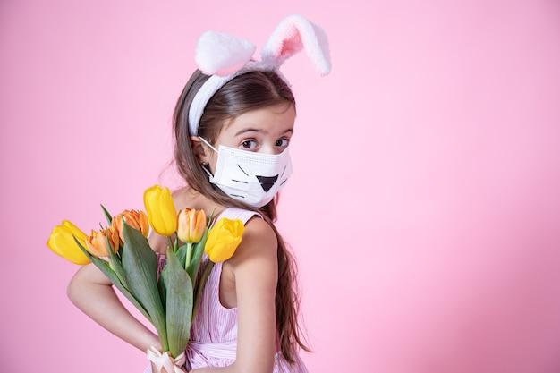 Маленькая девочка с ушками пасхального кролика и в медицинской маске держит в руках букет тюльпанов на розовом студийном фоне.
