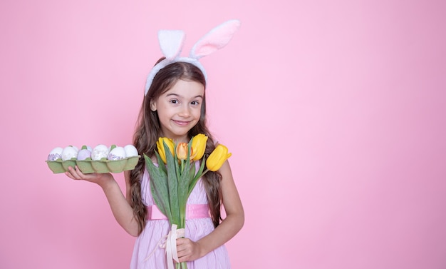 Маленькая девочка с ушками пасхального кролика держит в руках букет тюльпанов и поднос с яйцами на розовом студийном фоне