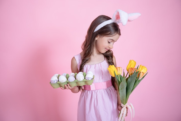 Little girl with easter bunny ears holds a bouquet of tulips and a tray of eggs in her hands on a pink studio background