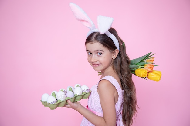 Little girl with easter bunny ears holds a bouquet of tulips and a tray of eggs in her hands on a pink wall.