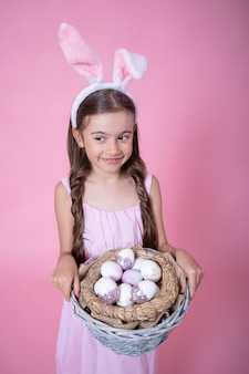 Little girl with easter bunny ears posing holding a basket with festive easter eggs on a pink wall close up.