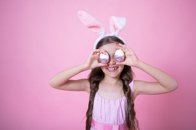 Маленькая девочка с ушками пасхального кролика позирует, держа в руках праздничные пасхальные яйца на розовом студийном фоне крупным планом