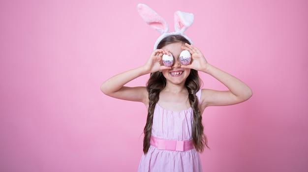 Маленькая девочка с ушками пасхального кролика позирует, держа в руках праздничные пасхальные яйца на розовом студийном фоне