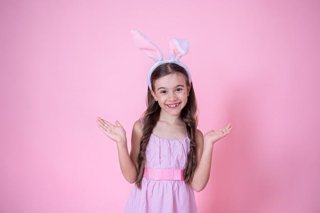 Маленькая девочка с ушками пасхального кролика позирует на розовом