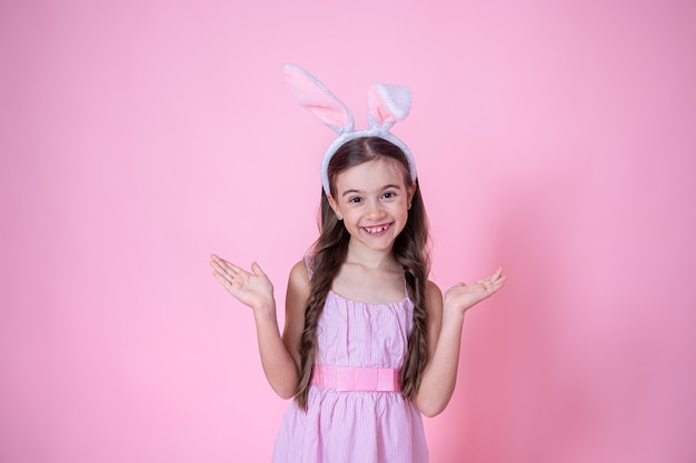 Little girl with easter bunny ears posing on pink