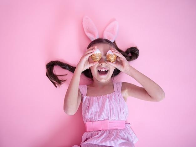 Маленькая девочка с ушами пасхального кролика позирует с праздничными пасхальными яйцами, лежащими на розовой стене.