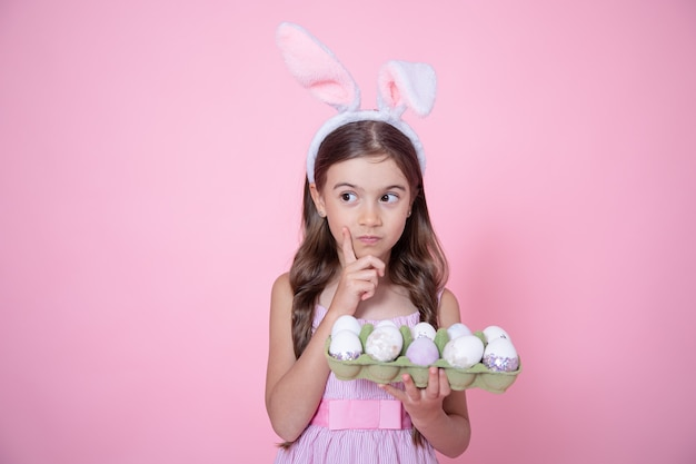 Little girl with easter bunny ears and a tray of eggs in her hands on pink