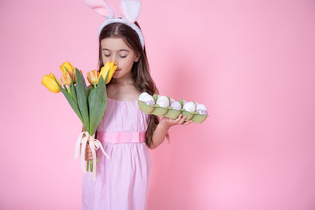 Little girl with easter bunny ears and a tray of eggs in her hands sniffing a bouquet of tulips on a pink studio background