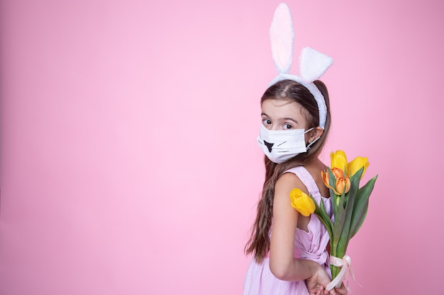 Little girl with easter bunny ears and wearing a medical face mask holds a bouquet of tulips in her hands on a pink