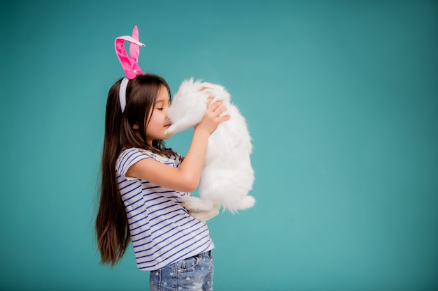 Little girl with easter bunny on yellow background