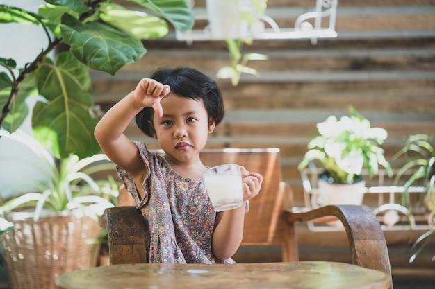 표정 얼굴을 가진 어린 소녀 어린 소녀의 개념은 우유를 마시는 것을 좋아하지 않습니다
