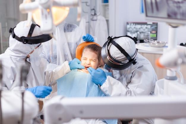 空洞治療の過程で痛みのために目を閉じた少女。子供の歯の処置をしているcovid19の間にppeスーツを着ている口腔病学チーム。