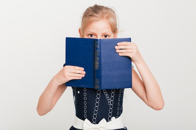 Little girl with face behind book