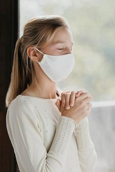 Bambina con maschera facciale in preghiera