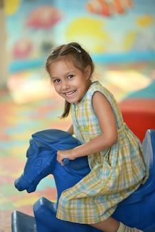 Маленькая девочка с ярмарочной лошадью в парке на открытом воздухе