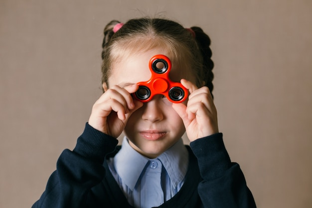 Little girl with fidget spinner held up to his eyes