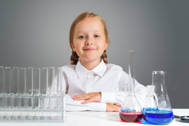 Little girl with flasks for chemistry sits at a table.