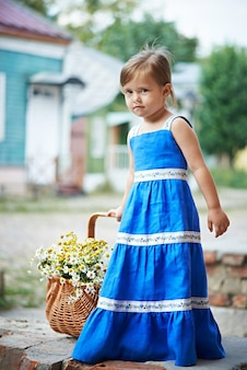 Little girl with flowers in basket