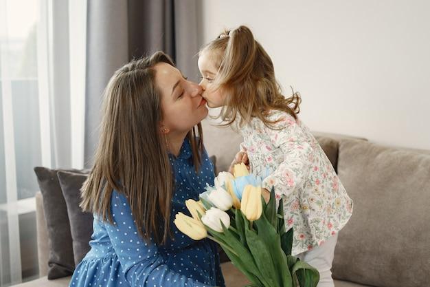 花を持つ少女。お母さんは妊娠しています。お母さんへのご挨拶。