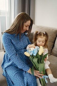 Little girl with flowers. mom is pregnant. greetings for mom.