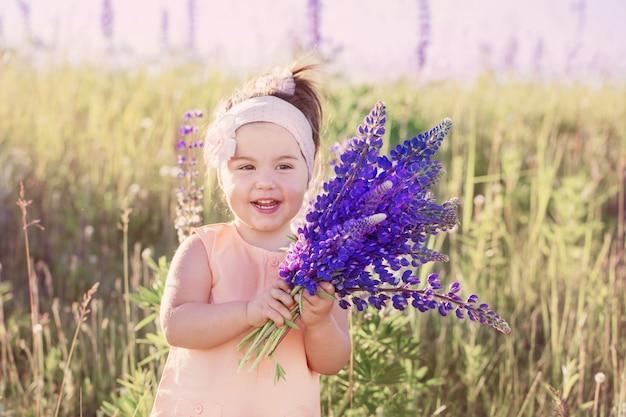Маленькая девочка с цветами на открытом воздухе