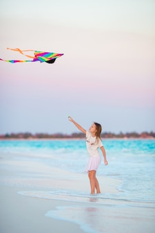 Little girl with flying kite on tropical beach.