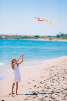Little girl with flying kite on a tropical beach