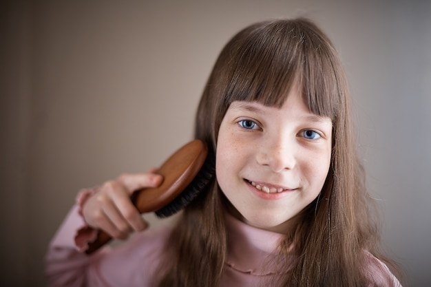 Little girl with freckles and blue eyes combing her hair