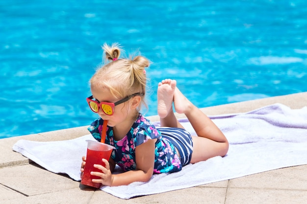 Little girl with fresh cocktail on swimming pool in the summer day