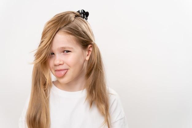 面白い収集された髪と舌を持つ少女は、白い背景に突き出ていました。子供のヘアカットとヘアスタイル。子供のためのシャンプーと化粧品。コピースペース