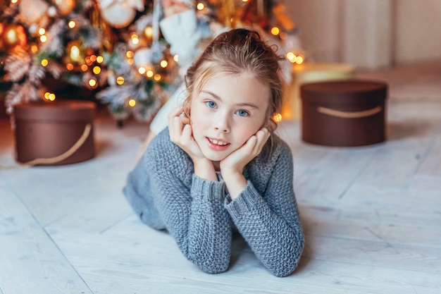 自宅のクリスマスツリーの近くにギフトボックスを持つ少女