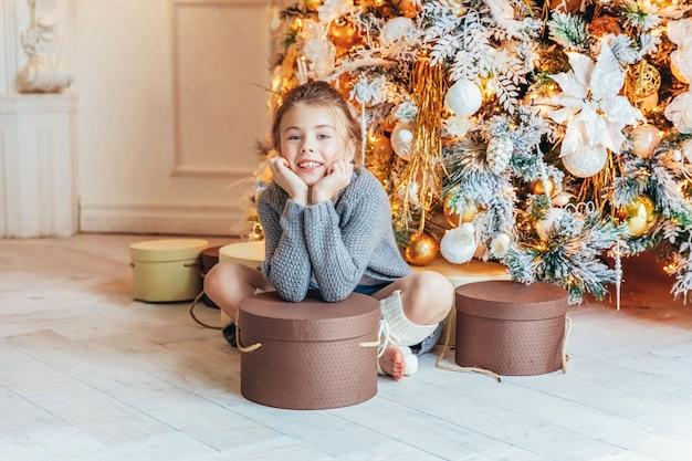Маленькая девочка с подарочной коробкой возле елки с зимним украшением дома