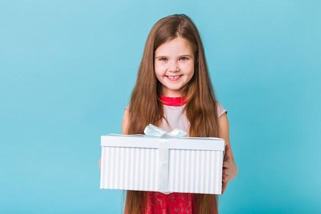 青い背景の上のギフトボックスを持つ少女