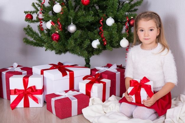 Little girl with gifts and decorated christmas tree at home