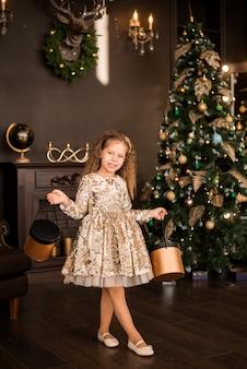 크리스마스 트리 배경에 선물을 가진 어린 소녀. 스마트한 골드 드레스를 입은 아이