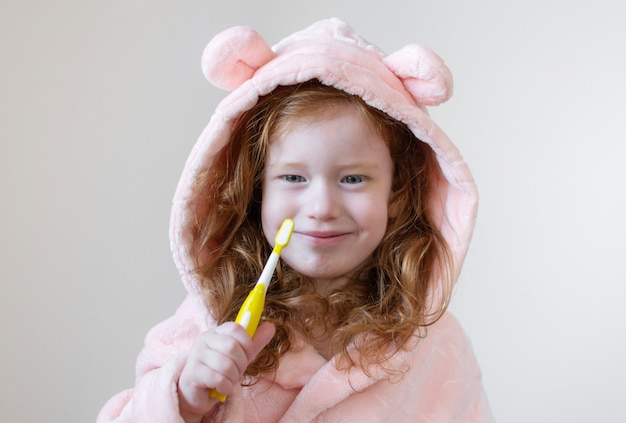 Little girl with ginger hair brushing her teeth, yellow toothbrush, dental hygiene, morning night healthy concept lifestyle