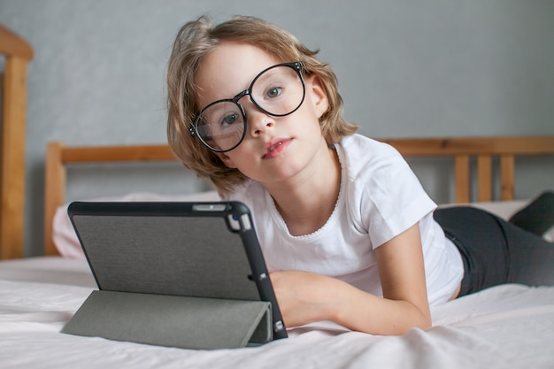 안경을 쓴 어린 소녀는 친척들과 집에서 침대에 누워 온라인으로 숙제를 한다