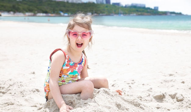 A little girl with glasses is playing in the sand on the beach by the sea.