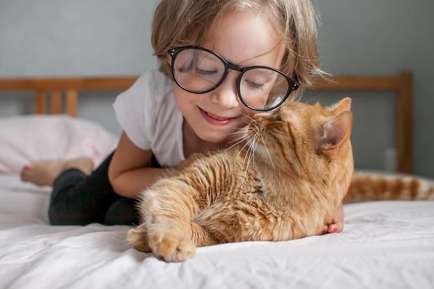 안경을 쓴 어린 소녀는 침대에 누워 뚱뚱한 생강 고양이를 껴안습니다.