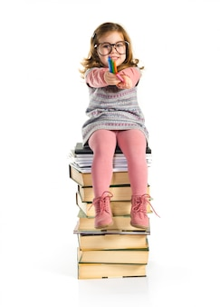 Little girl with glasses sitting on books. back to school